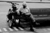 Man with bike on bench mono