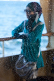 Woman through salt sprayed ferry window