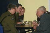 The young service men talk to the old veterans.. while enjoying a beer together.