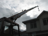 Reaching up over roof of house to back of house