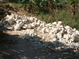 piles of rocks that have to be broken down into smaller pieces for the wall