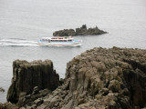 A sightseeing boat passing the rocks