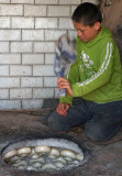 Boy Making Bagels in Old Clay Oven
