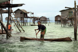 Pulau Bodgaya: Sea gypsy girl paddling her boat between the houses on stilts in the sea