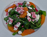 Arugula with orange slices, goat cheese, and pomegranate sauce