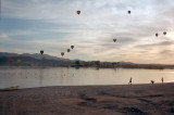 Kids playing at sunset as balloons float by