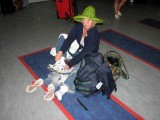 Judy on the Toronto Airport floor, taking the sand out of her shoes!!