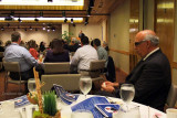 Sylvester Lukis speaking and Eli Mizrahi in the foreground at the Dick Judy Celebration of Life luncheon