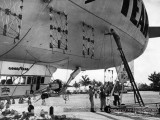 1947 - workers installing aerial signage on the side of the Goodyear Blimp Ranger NC-1A at Watson Island, Miami