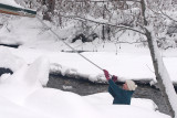 Marty  Raking Snow Off Her Roof ( Mad River In Backdrop )
