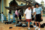 Tourists remove their shoes at the Cao Dai temple