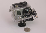 GO-PRO HERO2 (SPORTS EDITION), WITH THE OPTIONAL LCD UNIT  -  INSTALLED  IN THE SKELETON CASE WITH A TRIPOD MOUNT
