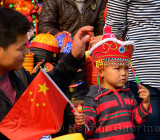 Father and son at a hat shop in Forbidden City Beijing with Chinese flag