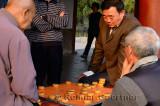 Group of men watching pair play Chinese Chess or Xiangqi in Beijing China