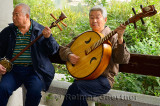 Two men playing a Chinese banjo and Ruan in an orchestra outdoors at Zizhuyuan Purple Bamboo Park in Beijing