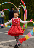 Young Chinese girl waving streamers at Zizhuyuan Purple Bamboo Park Beijing