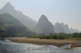 Pebble shore of the Li River with limestone Karst peaks receding into the haze