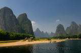 Boats and rest stop on the Li river China with tall karst formations receding into the distance