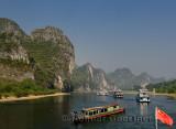 Cruise ships and rusted barge on the Li River Guangxi China with karst dome mountains