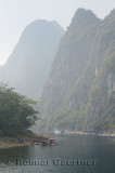 Cruise ship and sightseeing rafts on the hazy Li River in China among the tall karst peaks of Guangxi