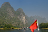 Chinese flag on a cruise ship on the Lijiang river Guangxi China with tall karst peaks