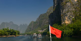 Chinese flag and cruise ships and sightseeing rafts on the Lijiang river Guangxi China with tall karst mountains