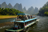 Tour boat cruise down the Li river with bamboo forest and hazy karst peaks