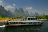 Chinese tour boat cruising down the Li river with bamboo forest and hazy karst peaks
