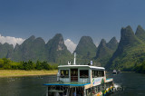 Chinese tour boats cruising the Li river Guangxi China with tall karst peaks