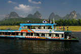 Chinese tour boat at Yangshuo on the Li river Guangxi China with bamboo and karst peaks