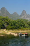 Farmers carrying goods to a bamboo raft with rusted barge and karst peaks on Li river China