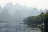 Barges rafts and cruise boats on the Li River Guangxi China with karst dome mountains in the haze