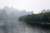 Tour boats on the Li River Guangxi China with karst dome mountains in the haze