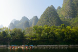 Tour boat rafts on the Li River Guangxi China with karst dome mountains in the haze