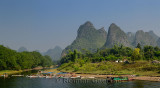 Tour boat rafts on the shore of the Li river Guangxi China with karst mountain peaks