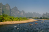 Row of tour boat rafts and a cruise ship heading up the Li river China with karst mountains