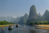Tour boats traveling down the Li river Guangxi China with tall karst mountain cones