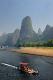 Tour boat raft traveling down the Li river Guangxi China with tall karst mountain cones