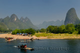 Tour boat rafts at rest stop on the Li river Guangxi China with tall karst mountain cones