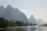 Tour boat rafts heading down the Li river Guangxi China with tall karst mountain cones in haze