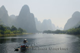 Tour boat rafts on the Li river Guangxi China with tall karst mountain peaks receding in the haze
