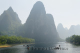 Tour boat rafts on the Li river Guangxi China with sugarcone karst mountain peaks receding in the haze