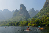 Tour boat rafts on the Li river Guangxi China with pointy karst mountain peaks in the haze