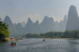 Tour boat rafts on the Li river Guangxi China with fingerlike karst mountain peaks in the haze