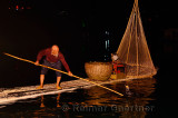 Chinese fisherman lifting Cormorant with fish onto the raft on the Li river in Yangshuo China at night