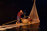Chinese night fisherman lifting Cormorant with fish into a basket on the Li river in Yangshuo China
