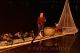 Chinese fisherman with cormorants and net on a raft in Yangshuo China at night on the Li river