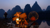 Cormorant fisherman tending lantern with birds on bamboo raft at dawn on the shore of the Li river Yangshuo China
