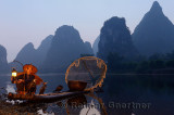 Cormorant fisherman lighting lamp with birds on bamboo raft at dawn on the shore of the Li river Yangshuo China