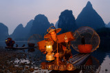 Fisherman moving cormorant by the head on a bamboo raft by the shore of the Li river Yangshuo China